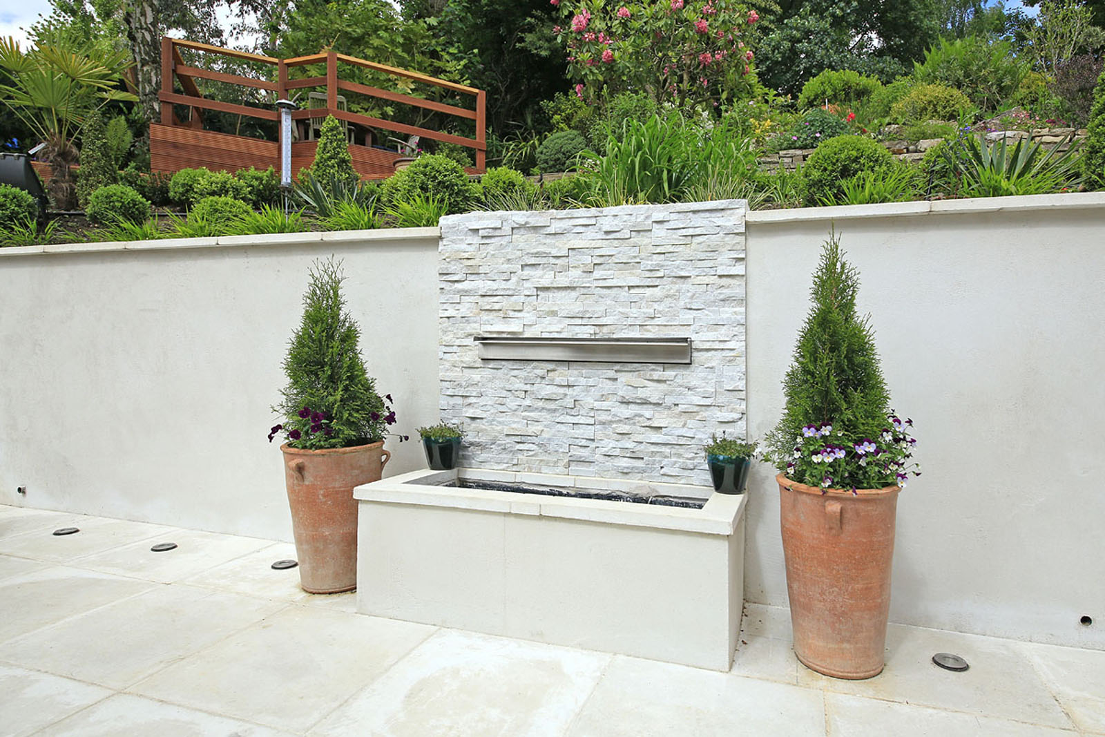 The Garden Was Completely Cleared And Floor Paved With Designer White Paving Slabs Complete Water Feature A Decked Seating Area
